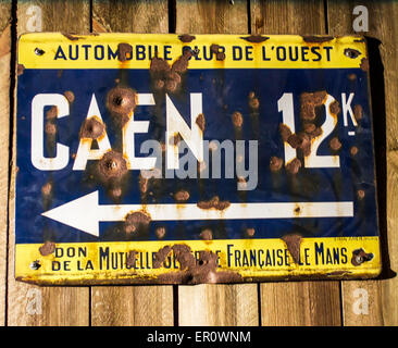 An original vintage bullet pocked metal sign from World War II France indicating the direction to Caen. - Stock Photo