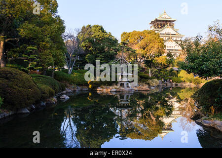 Osaka castle keep, borogata style, towering above the Japanese garden of the Kishu Palace and reflected in the pond. Stone lantern in foreground.