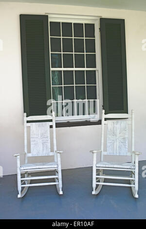 A pair of white antique rocking chairs await visitors to Melrose, an Old South antebellum mansion in Natchez, Mississippi, - Stock Photo