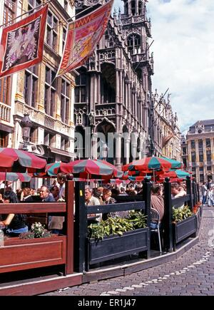 Tourists relaxing at a pavement cafe outside the Maison du Roi (Kings House) in the Grand Place, Brussels, Belgium, - Stock Photo