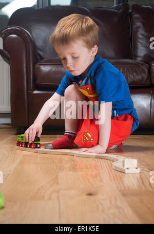Young boy (age 3 - 4 years) playing with a wooden train - Stock Photo