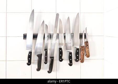 Set of knives on magnetic holder on white tiles - Stock Photo