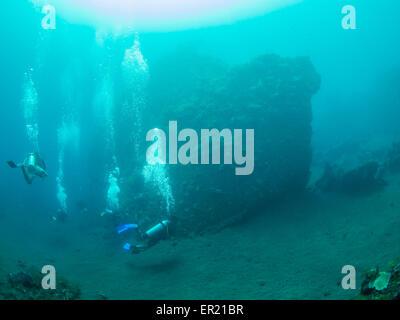 Group of scuba divers exploring the famous ship wreck USS Liberty at Tulamben on Bali, Indonesia - Stock Photo