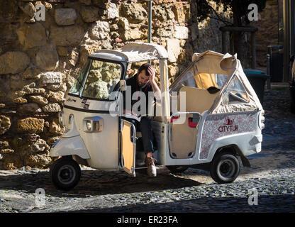 Tuk Tuk and driver in the Street close to Sao Jorge Sastle in Lisbon - Stock Photo