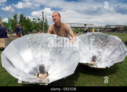 Berlin, Germany. 25th May, 2015. Rolf aligns two self-built solar umbrellas for cooking noodles and tomato sauce - Stock Photo