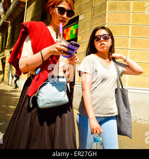 Two young asian women with sunglasses walking along street. Barcelona, Catalonia, Spain. - Stock Photo