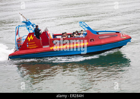Visitors enjoying a ride on Shockwave boat at Bournemouth Bay, Dorset in May - Stock Photo
