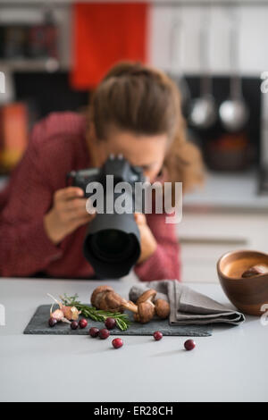 A woman photographer is leaning down, taking a close-up of autumn fruits and vegetables - mushrooms, garlic, rosemary, - Stock Photo