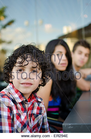 Three Hispanic children waiting for dinner in a restaurant's patio in Toronto, close up of curly haired boy in checkered - Stock Photo