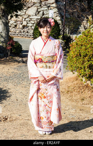 Japan. Japanese young woman standing posing in pink kimono, hands together, smiling. Flower in her hair - Stock Photo