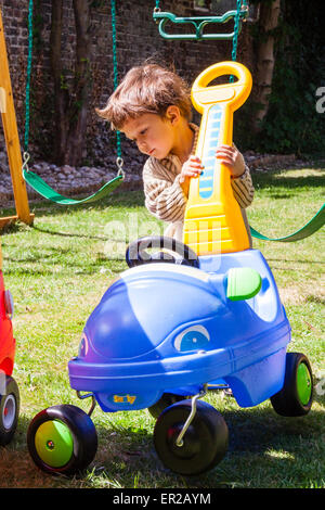 3 - 5 year old Caucasian child, boy. Outdoors in a garden, pushing pedal car around, hair wind blown - Stock Photo