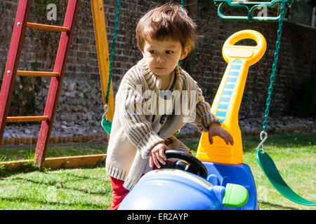 3 - 5 year old Caucasian child, boy. Outdoors in a garden, pushing pedal car around - Stock Photo