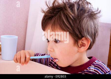 3 - 5 year old Caucasian child, boy. Side-view, head and shoulder, holding toothbrush and brushing teeth - Stock Photo