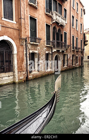 Prow of a Venetian gondola on a rainy day in a small canal in Venice, Italy, with historic buildings and old water - Stock Photo