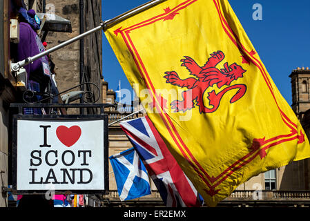 Lion Rampant, Union Jack and the Scottish Saltire flying outside a tourist souvenir shop in Edinburgh's Old Town. - Stock Photo