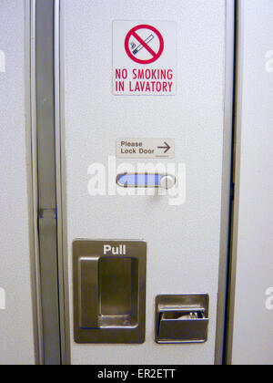 Airplane toilet door with No Smoking warning signs beside ...