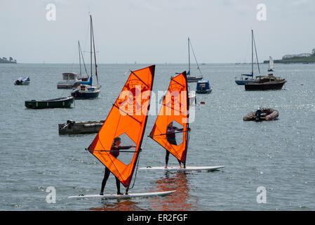 Two individuals learning to windsurf at Loe Beack, Feock near Falmouth, Cornwall. - Stock Photo