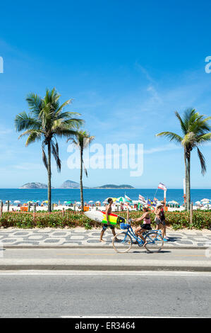 RIO DE JANEIRO, BRAZIL - MARCH 08, 2015: Brazilians walk and ride bicycles with surfboards on the beachfront boardwalk - Stock Photo