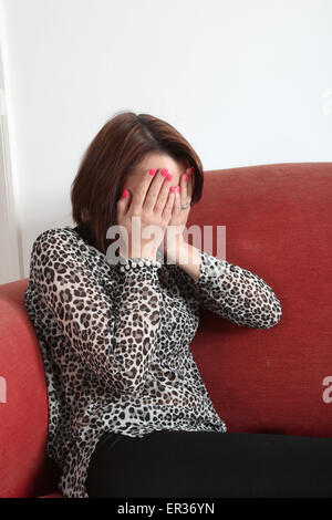 Young woman alone on a red sofa, hands covering her face in despair.. - Stock Photo