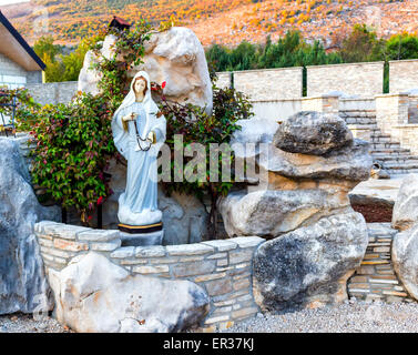 ... Statue Of The Blessed Virgin Mary With Wooden Prayer Beads Necklace In  A House Rock Garden