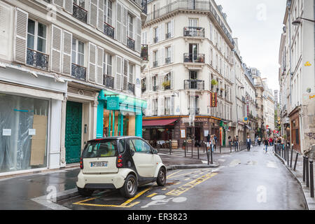 Paris, France - August 10, 2014: small white Smart car stands on the street in Paris, tourists walk on Rue St. Andre - Stock Photo