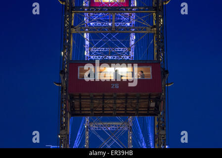 Riesenrad Prater carriage, visitors to the Prater amusement park enjoy a night time ride on the famous Riesenrad - Stock Photo