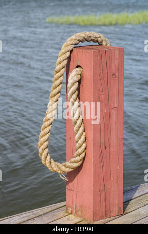 Red wooden boat bollard and rope on edge wooden dock - Stock Photo