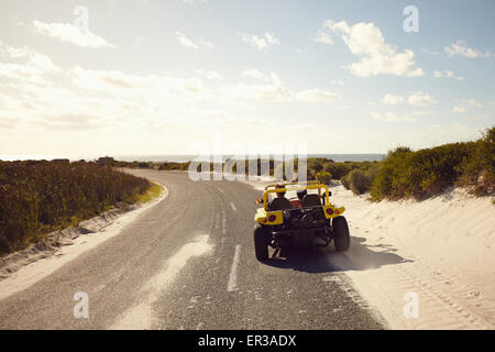 Rear view of young couple driving down a open road to the beach on a sunny day. Couple on road trip in a small car. - Stock Photo