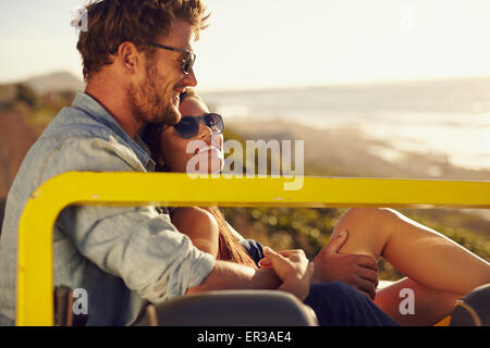 Portrait of beautiful young couple sitting together in a car smiling on a summer day. Romantic young couple enjoying - Stock Photo
