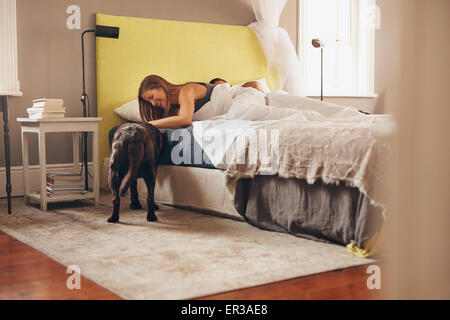 Woman lying on bed playing with her pet dog in morning. Man sleeping in background. - Stock Photo