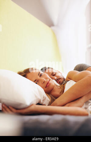 Young couple lying together on bed. Beautiful young woman lying on bed and looking at camera with her husband sleeping. - Stock Photo