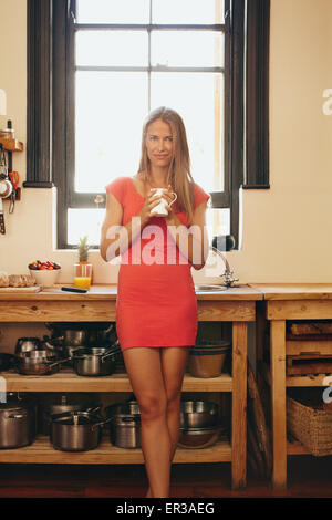 Portrait of young woman standing in kitchen holding a hot and fresh cup of coffee. Caucasian female model in short - Stock Photo