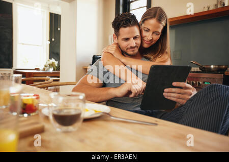 Indoor shot of young caucasian couple in the kitchen in the morning and using a digital tablet together. - Stock Photo