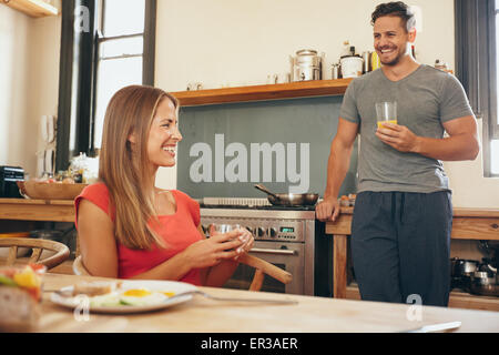 Shot of young couple in kitchen smiling. Young woman sitting at breakfast table with man standing by kitchen counter - Stock Photo