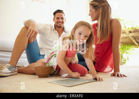 Indoor shot of cute little girl painting with her parents sitting behind her. Family sitting on floor in living - Stock Photo