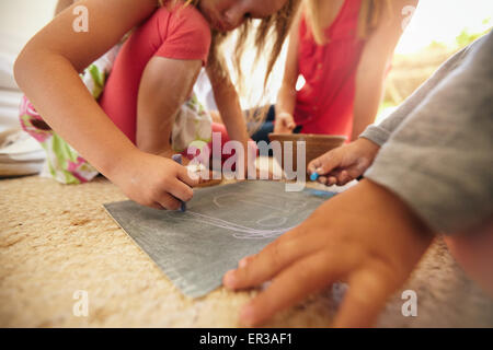Little girl drawing with her brother and parents sitting by. Focus on girls hands drawing with chalk colors. - Stock Photo