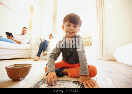 Cute little boy drawing and coloring with his father and mother sitting on sofa using digital tablet. Boy sitting - Stock Photo