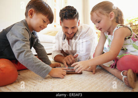 Father with son and daughter sitting on floor using digital tablet indoors. Happy young family together at home - Stock Photo
