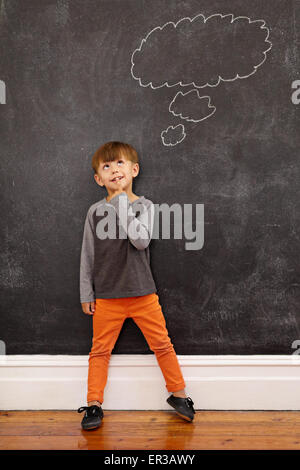 Child thinking with a thought bubble on the blackboard. Full length shot of cute little boy standing at home. Inspiration - Stock Photo