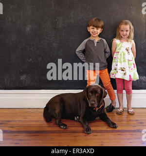 Full length shot of smiling little boy and girl standing next to dog at home. Labrador retriever sitting on floor - Stock Photo
