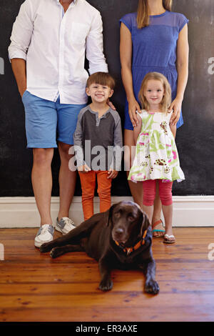 Cropped shot of lovely young family with their pet dog. Labrador retriever sitting on floor with kids and their - Stock Photo