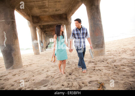 Couple holding hands, walking barefoot  under a pier