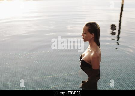 Woman standing in a swimming pool - Stock Photo