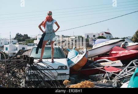 Woman standing on car in scrap yard - Stock Photo