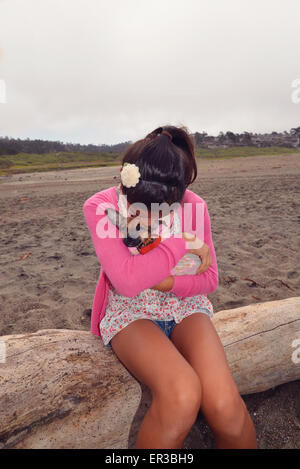 Girl sitting on a tree trunk cuddling puppy - Stock Photo
