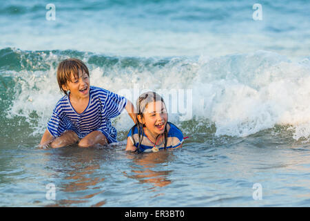 Two children playing in the sea - Stock Photo