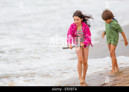 Boy and girl walking on the beach - Stock Photo