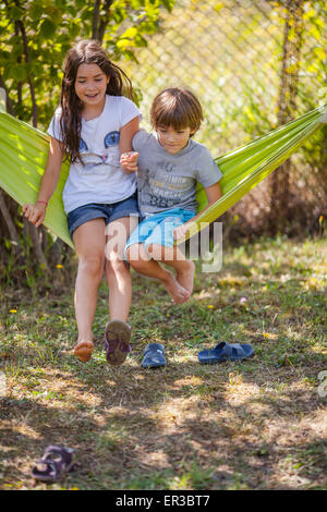 Boy and girl sitting on a hammock  in the garden - Stock Photo