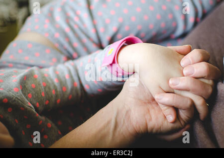 Mother and daughter sitting together and holding hands - Stock Photo
