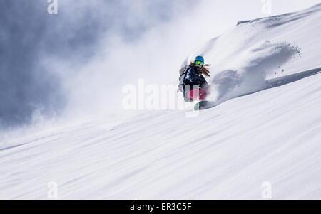 Girl Snowboarding in fresh powder snow, Gastein, Salzburg, Austria - Stock Photo